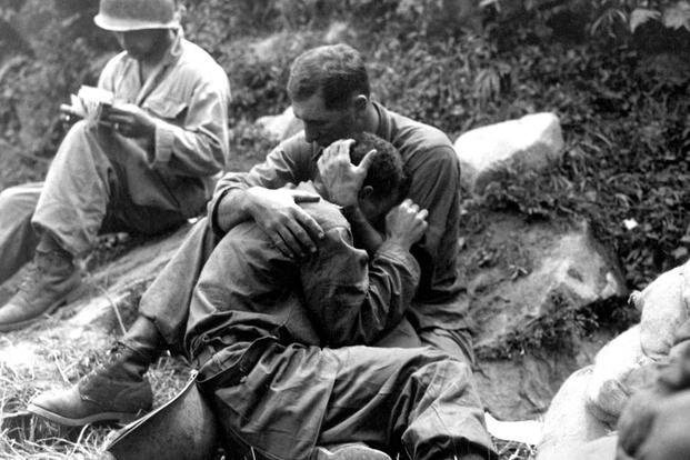 A G.I. comforting a grieving infantryman in the Korean War. (U.S. Army/ Sergeant 1st Class Al Chang)